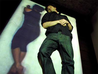 Foto de un hombre tumbado en una cama sobre la que se proyecta la imagen de una mujer acostada a su lado