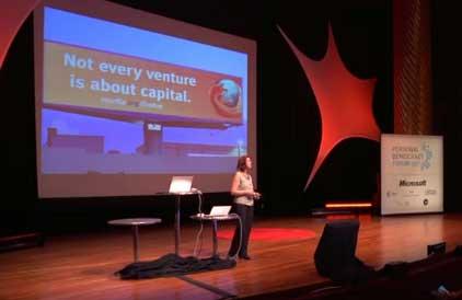 Captura de la diapositiva que muestra la oradora. Cartel publicitario de Mozilla con la leyenda (en inglés) 'Not every venture is about capital''