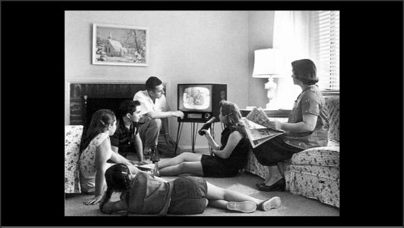 Foto en blanco y negro de un pequeño grupo de personas alrededor de una televisión