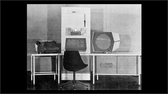 Foto de un ordenador antiguo. Del tamaño de una nevera y con una pantalla muy rudimentaria