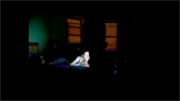 Foto de una chica en la oscuridad, tumbada en la cama, con la cara iluminada por lo que parece ser una pantalla que está mirando