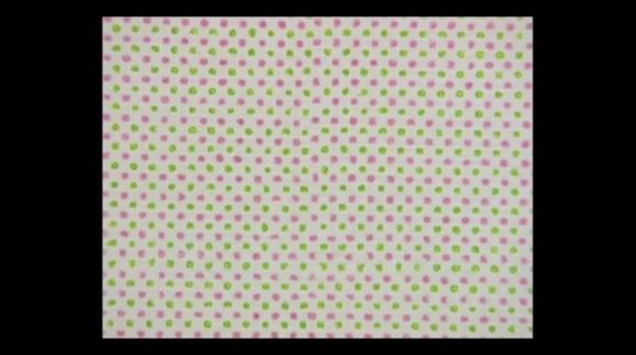 Primerísimo primer plano de un cuadro abstracto. Puntos verdes y rojos en un patrón regular