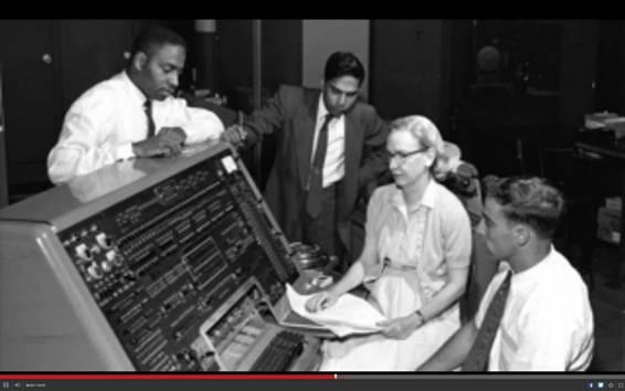 Grace Hopper sentada frente a la consola de un ordenador de la época en compañía de tres hombres